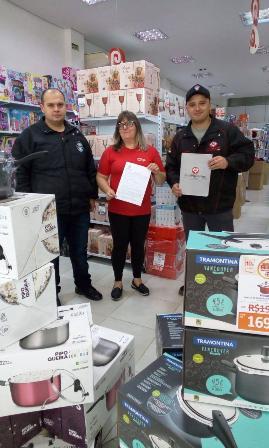 Representante do sindicato, Eduardo Blauth, à direita, com Liziane dos Santos, funcionária da loja, e o vigilante Carlos Donato